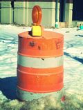 Orange construction barrel in winter. A single orange barrel, with reflectors, with a background of winter snow, construction even happens when it's cold outside Royalty Free Stock Photos
