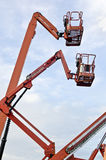 Orange construction crane baskets Stock Photo