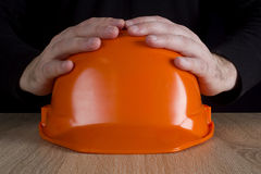 Orange construction helmet in hands Stock Image