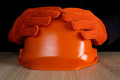 Orange construction helmet in hands Royalty Free Stock Photos
