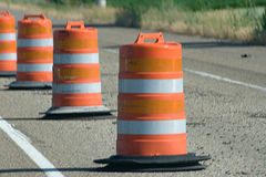 Orange Construction Warning Barrels. Is a row of barrel cones that are bright orange on the highway Stock Photo