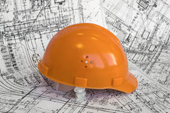 Orange constructional helmet and project drawings. Business objects on the construction dimensioned drawing Stock Photo