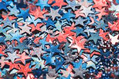 Orange coral and blue star shaped festive confetti background royalty free stock images