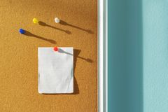 Orange Cork board with one paper note pinned and several different color pins above with shadows from the side sunlight through stock photos