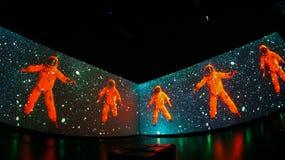 Orange cosmonauts among stars in space stock photography