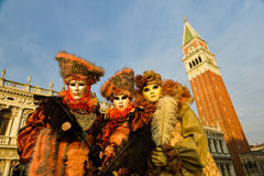 Orange costumed masked group. In front of Campanile in Venice at sunrise Royalty Free Stock Images