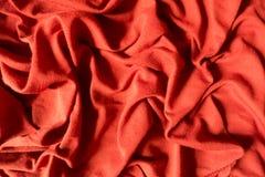 Orange cotton fabric in soft folds. Orange cotton jersey fabric in soft folds Stock Photo