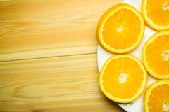 Orange coupée en tranches d'un plat blanc sur un fond en bois Image stock