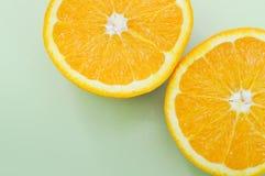 Orange coupée en tranches sur un fond vert images libres de droits