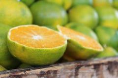Orange coupée en tranches sur une pile des oranges vertes dans une boîte en bois au marché Photo stock