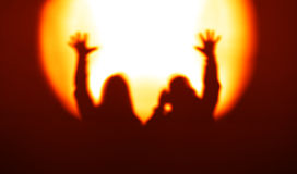 Orange couple silhouettes with hands up in light of floodlight b royalty free stock photography