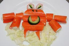 Orange crab of crab sticks on a white plate. Crab of sticks, edi. Ble, on a plate. Food for children. Crab sticks Royalty Free Stock Photography