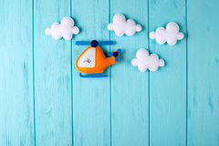 Orange craft helicopter and clouds on blue wooden background with copyspace. Felt handmade toys. Empty space for text. Top view. Stock Photos