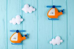 Orange craft helicopter and clouds on blue wooden background with copyspace. Felt handmade toys. Empty space for text. Top view. Concept for travel agency Stock Photo