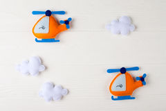 Orange craft helicopter and clouds on white wooden background with copyspace. Felt handmade toys. Empty space for text. Top view. Royalty Free Stock Photos