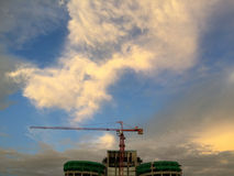 Orange crane and green cover over construction building. Orange crane and green plastic cover over construction building on the bottom, above is beautiful cloudy Stock Photo