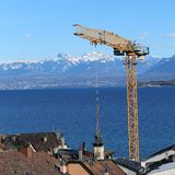 Orange Crane with Stunning Landscape with Swiss Alps in the Background royalty free stock photo