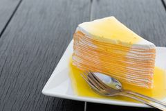 Orange crepe cake in white dish on black wooden table.  stock images