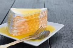 Orange crepe cake in white dish on black wooden table.  stock photos