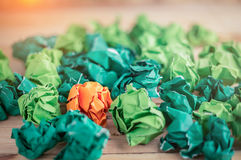 Orange crumpled paper among the green pape Royalty Free Stock Photos
