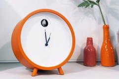 Orange cuckoo alarm clock in modern interior royalty free stock photography