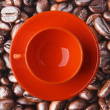 Orange cup on the coffee beans. Royalty Free Stock Photos