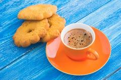 orange cup of coffee witt tasty cookie Royalty Free Stock Image
