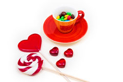 Orange cup with colorful button-shaped chocolates and lollipops. Stock Photo