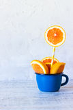 Orange in a cup. Place in the text. Fresh orange slices in blue enamel mug Stock Image