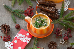 An orange cup of pumpkin soup, several slices of rye bread, pieces of fresh pumpkin and winter decoration elements on a coarse clo Stock Photography