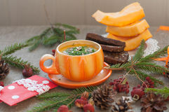 An orange cup of pumpkin soup, several slices of rye bread, pieces of fresh pumpkin and winter decoration elements on a coarse clo Royalty Free Stock Photo