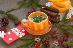 An orange cup of pumpkin soup, several slices of rye bread, pieces of fresh pumpkin and winter decoration elements on a coarse clo Stock Images