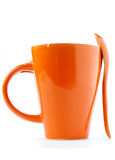 Orange cup and spoon Royalty Free Stock Images