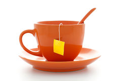 Orange cup with tea bag. Orange cup of tea with saucer and tea bag inside with empty yellow label Stock Photos
