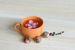 Orange Cup of tea with flower and floral tea Royalty Free Stock Photos