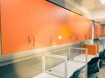 Orange cupboards in an office. With white tables and sections for desktop computers and office work stock images