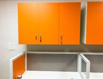 Orange cupboards in an office. With white tables and sections for desktop computers and office work royalty free stock images