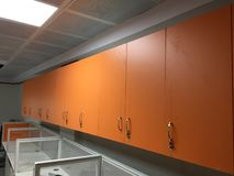Orange cupboards in an office. With white tables and sections for desktop computers and office work royalty free stock photography