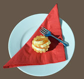 Orange cupcake and fork on plate with red serviette. A cupcake topped with orange slices on a red serviette sitting on a plate beside a silver cake fork royalty free stock image