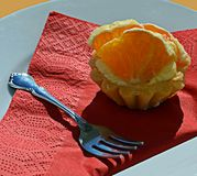 Orange cupcake and fork on plate with red serviette. A cupcake topped with orange slices on a red serviette sitting on a plate beside a silver cake fork stock images