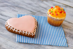 Orange cupcake and heart biscuit. Royalty Free Stock Photography