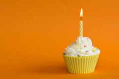 Orange cupcake. Yellow cupcake with burning candle and orange background Royalty Free Stock Images