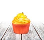 Orange cupcake with yellow cream Royalty Free Stock Image