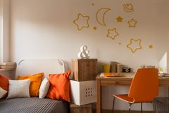 Orange cushions and chair. In teenager's room royalty free stock photo