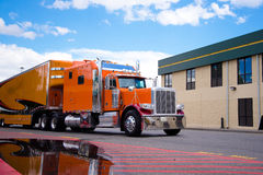 Orange custom semi truck big rig trailer drive on truck stop Royalty Free Stock Image