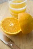 Orange cut with juice. Half of orange cut with knife and orange juice Royalty Free Stock Photos