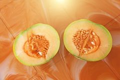 Orange cut melon with seeds inside. Two halves of a beautiful me. Lon. Tropical Asian fruits. Healthy food, natural fruits. View from above royalty free stock photos