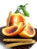 An orange cut in pieces. With cinnamon sticks royalty free stock photo