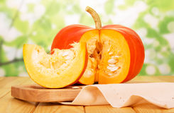 Orange cut pumpkin with seeds, and slice on abstract green. Stock Photos