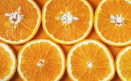 Orange cut into slices on an orange background royalty free stock images